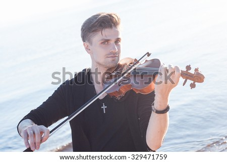 Violinist playing a violin,  young man plays on the background of  sea - stock photo