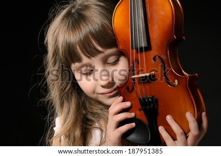 violinist playing the violin. photo session in studio on black background - stock photo