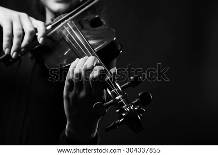 Violinist playing violin on dark background - stock photo
