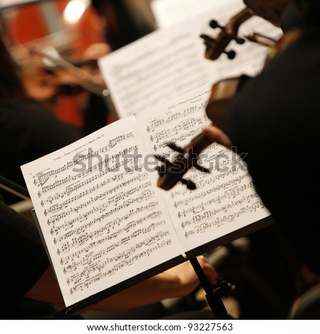 violinists during a classical concert music, focus on sheet music - stock photo