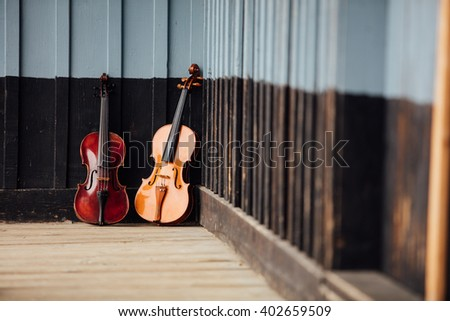 violins resting on an old wooden porch - stock photo