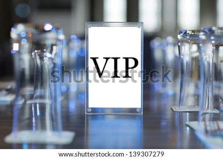VIP tag on table in resterant with blue lighting and bokeh - stock photo