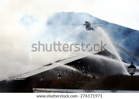 VIPITENO, ITALY - MAY 8, 2015: Volunteers Firefighters control burning down an old barn in mountain zone. Highest platform of a fire truck during a fire emergency in Vipiteno on May 8, 2015. - stock photo