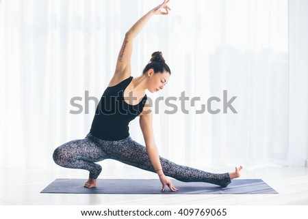 Virabadrasana. Beautiful yoga woman practice in a training hall background. Yoga concept. - stock photo
