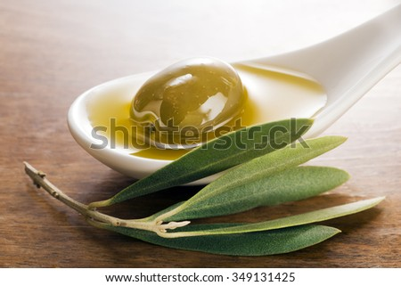 Virgin olive oil and olive fruit on white spoon close up. - stock photo