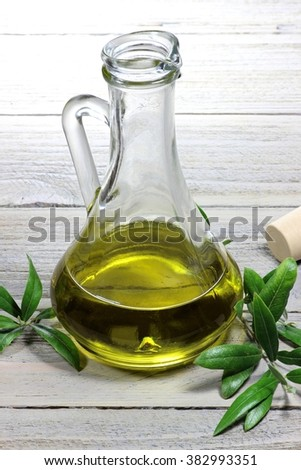 virgin olive oil in an glass carafe on wooden background - stock photo