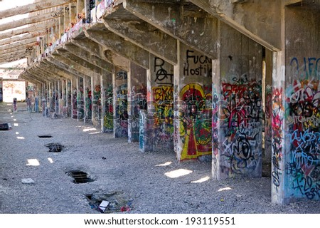 VIRGINIA CITY, NEVADA - APRIL 1, 2009:  Several years worth of graffiti on the support pillars of the abandoned 100 year old American Flats gold and silver cyanide mill and smelter. - stock photo