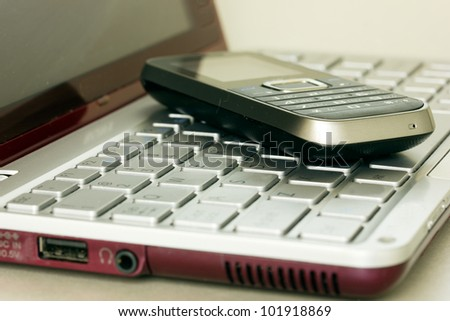 virtual banking concept - mobile phone over laptop keyboard
