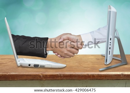 Virtual handshake. Internet business concept on wood table. - stock photo