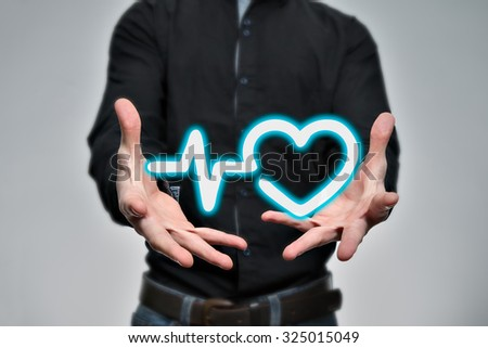 Virtual heart in hands as a symbol of health - stock photo