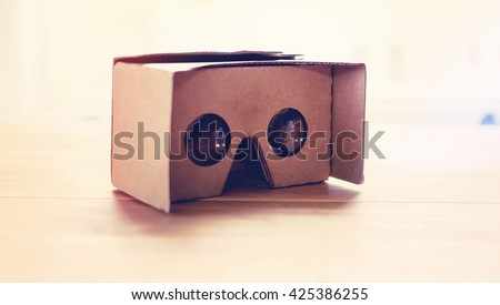 Virtual reality cardboard headset on a table in natural light - stock photo