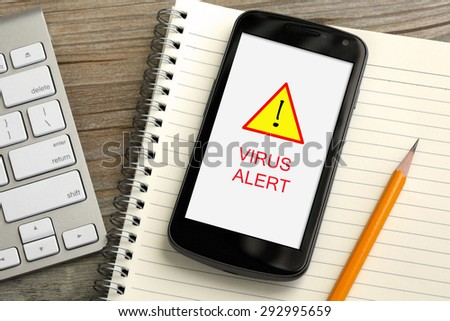 virus threat on mobile phone, with desk background - stock photo