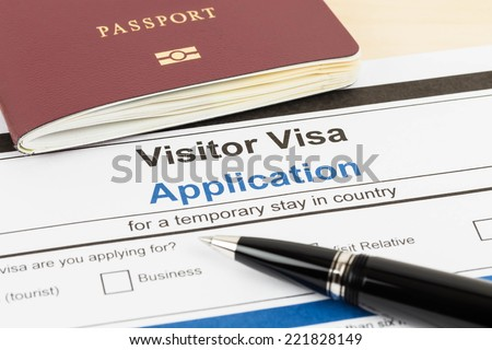Visa application form with passport and pen - stock photo