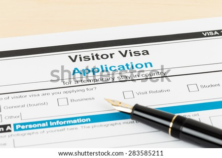 Visa application form with pen; form is mock-up