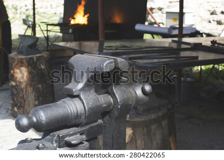 Vise and anvil in a forge shop. Blacksmith tools - stock photo