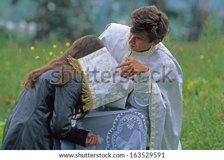 VISEU DE JOS, MARAMURES, ROMANIA - AUGUST 27: woman and pope at orthodox event on August 27, 2000 in Viseu de Jos, Maramures, Romania. The orthodox events are important part of Romanian culture.