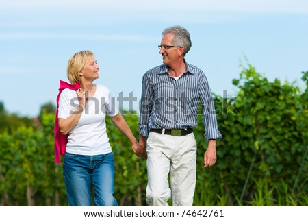 Visibly happy mature or senior couple outdoors hand in hand having a walk - stock photo