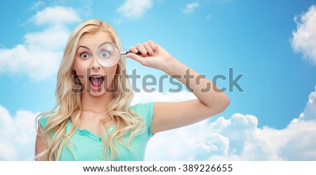 vision, exploration, investigation, education and people concept - happy smiling young woman or teenage girl looking through magnifying glass over blue sky and clouds background - stock photo