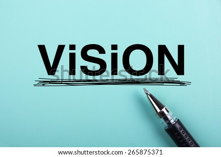 Vision text is on blue paper with black ball-point pen aside. - stock photo