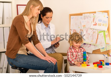 Visit at pediatrician observe child girl play at medical office - stock photo