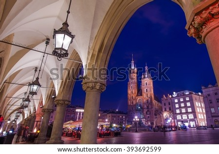 Visiting Cracow Poland. Krakow Old Town Sukiennice Marketplace and the St. Mary's Church. Mariacki Church. - stock photo