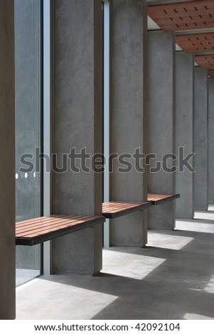 Visitor waiting area in a modern building, timber seats mounted into concrete structure - stock photo