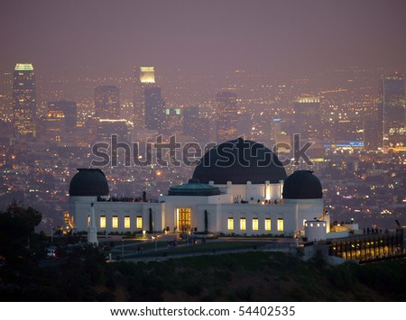 Visitors flock to Los Angeles's city owned Griffith Park Observatory on a slightly foggy night. - stock photo