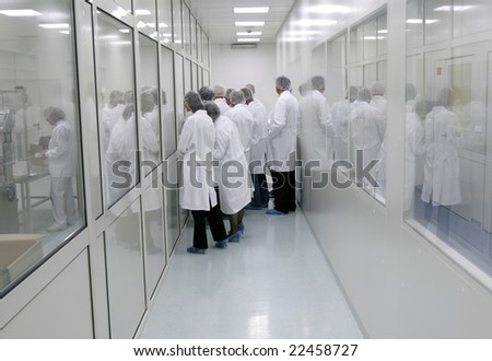 visitors in white coats in interior of a pharmaceutical industry - stock photo