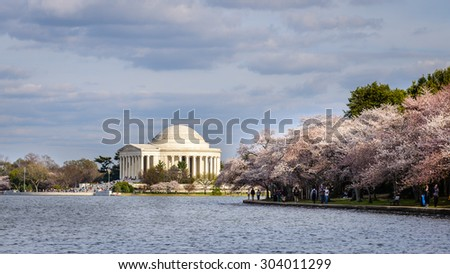 Visitors walk around the Tidal Basin, with the Jefferson Memorial in the background, during the Cherry Blossoms Festival in Washington DC. Photograph shot on April 8, 2014