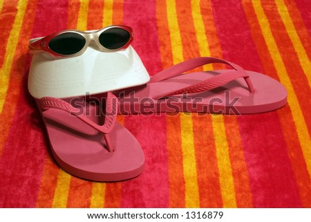 visor,sun glasses and beach shoes on colorful towel