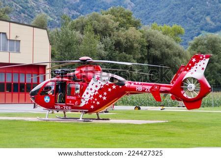 VISP, SWITZERLAND - AUGUST 12: Helicopter supplying the mountain huts in the mountains around Zermatt in Visp, Switzerland on August 12, 2014. - stock photo