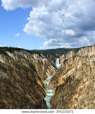 Vista shows the Grand Canyon of the Yellowstone, in Yellowstone National Park.  Yellow and pink tinted canyon walls lead to Lower Falls. - stock photo