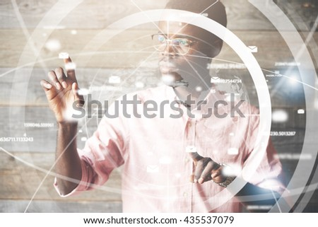 Visual effects. Future technology touch screen interface. High technology concept. Serious African American office worker using futuristic digital device, pointing on sensor screen. Selective focus - stock photo