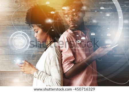Visual effects. Young African couple standing back-to-back, holding mobile phones. Jealous possessive man looking over his shoulder at his girlfriend's phone screen trying to see who she is messaging - stock photo