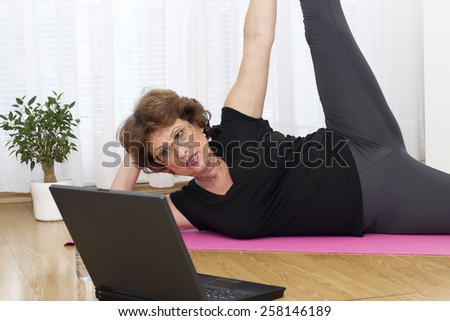 Vitality senior brown haired woman lying on the parquet floor and exercise using a laptop at home. - stock photo