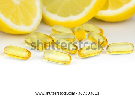 vitamin c pills and lemon slices on white background - stock photo