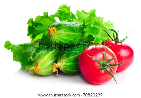 Vitamin collection of vegetables tomatoes and cucumbers with a branch and leaves of green salad on a white background - stock photo
