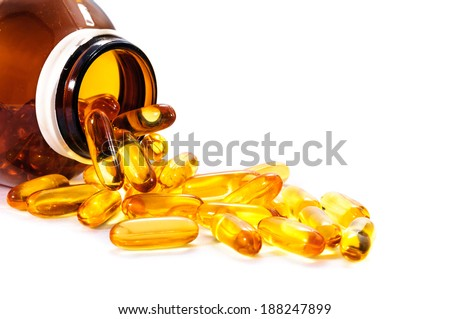 Vitamin D bottle with spilled contents on white - stock photo