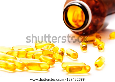 Vitamin D  spilled contents on white background - stock photo