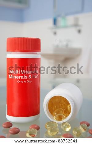 Vitamin pills on bathroom shelf - stock photo