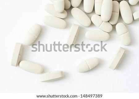 vitamin pills on white surface - stock photo