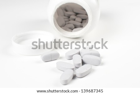 Vitamin pills out of bottle isolated