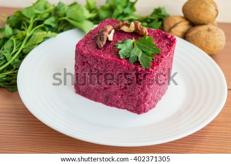 Vitamin salad of boiled beets in the form of a square, with walnuts on a white plate.  - stock photo