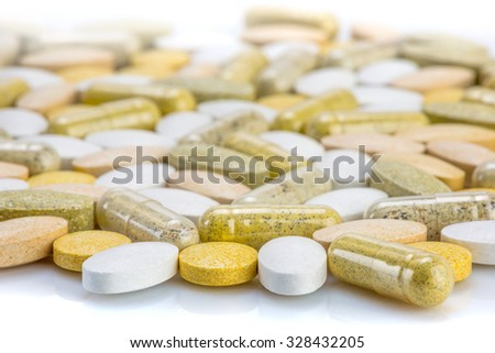 Vitamin supplements - capsules and pills on a white surface - stock photo