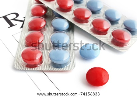 Vitamins and minerals in blue and red tablets and a blank prescription - stock photo