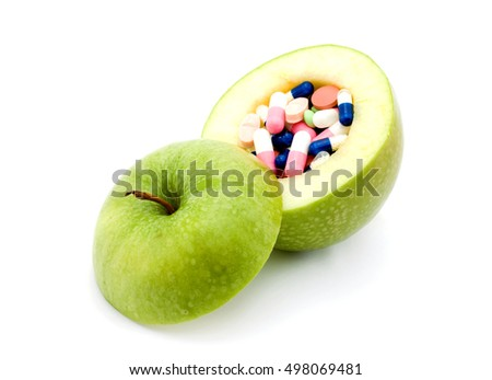 vitamins concept - apple and pills inside it studio isolated
