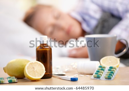 Vitamins, medicines and hot tea in front, woman caught cold sleeping in background.? - stock photo