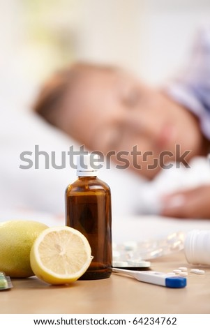 Vitamins, medicines and lemons in front, woman caught cold sleeping in background.? - stock photo