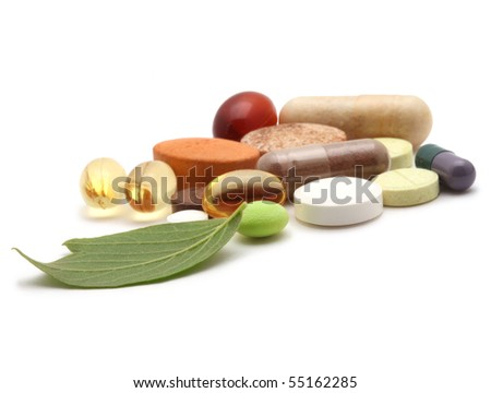 vitamins, tablets and pills and green leaf - stock photo