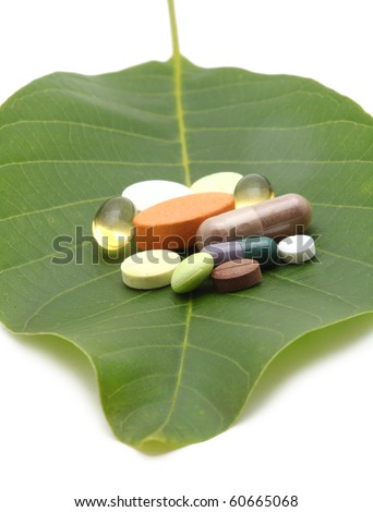 vitamins, tablets and pills on green leaf - stock photo